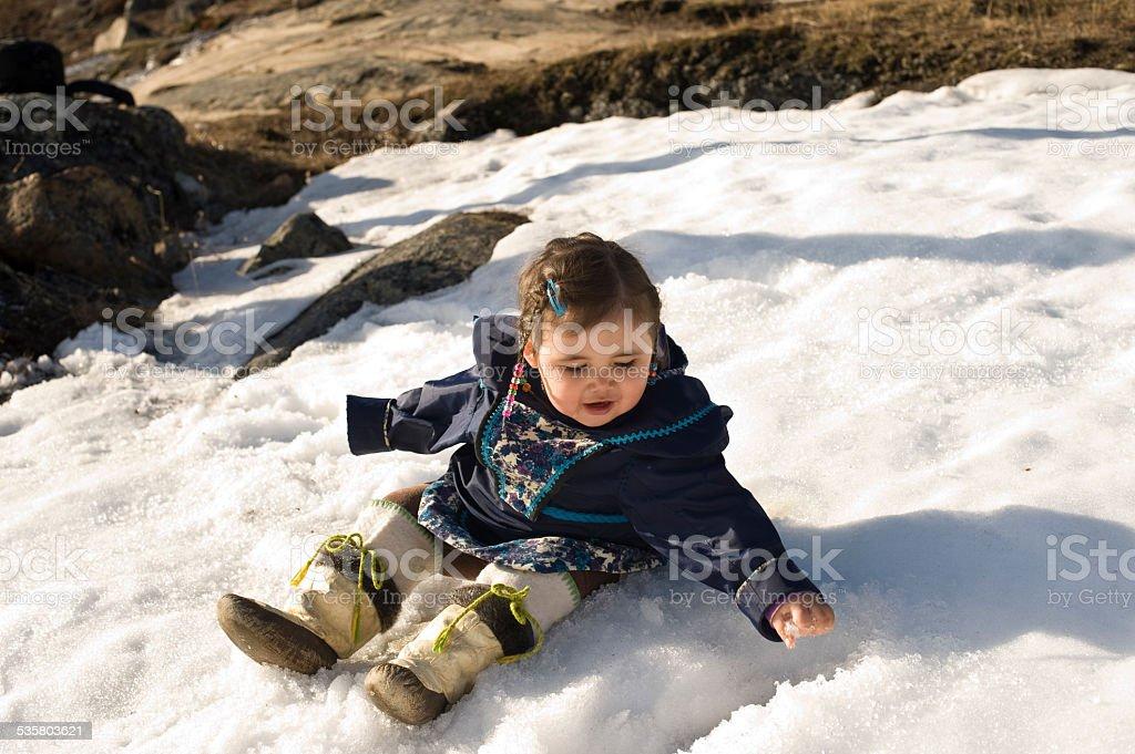 Inuit Child in the Snow, Baffin Island, Nunavut, Canada. stock photo