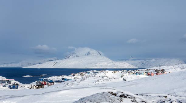 Inuit Häuser und Hütten verstreut über Schneetundra-Landschaft in Wohnort von Nuuk Stadt mit Fjord und Bergen im Hintergrund, Grönland – Foto