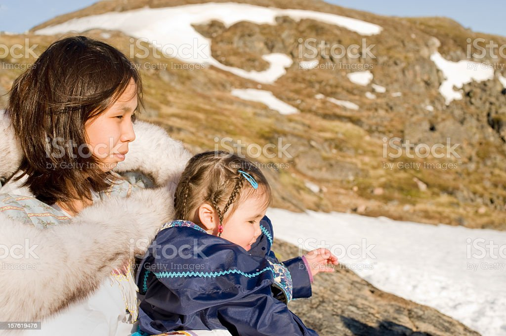 Inuit Mother and Daughter in Traditional Parkas, Nunavut. stock photo