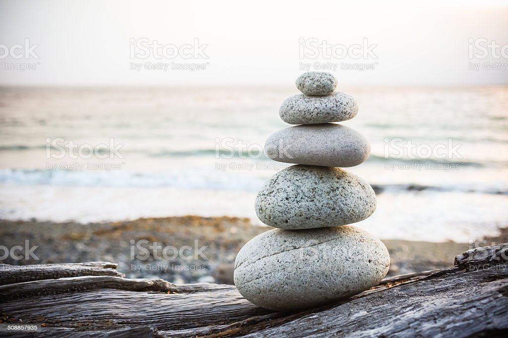 Inukshuk Cairn on driftwood on beach stock photo