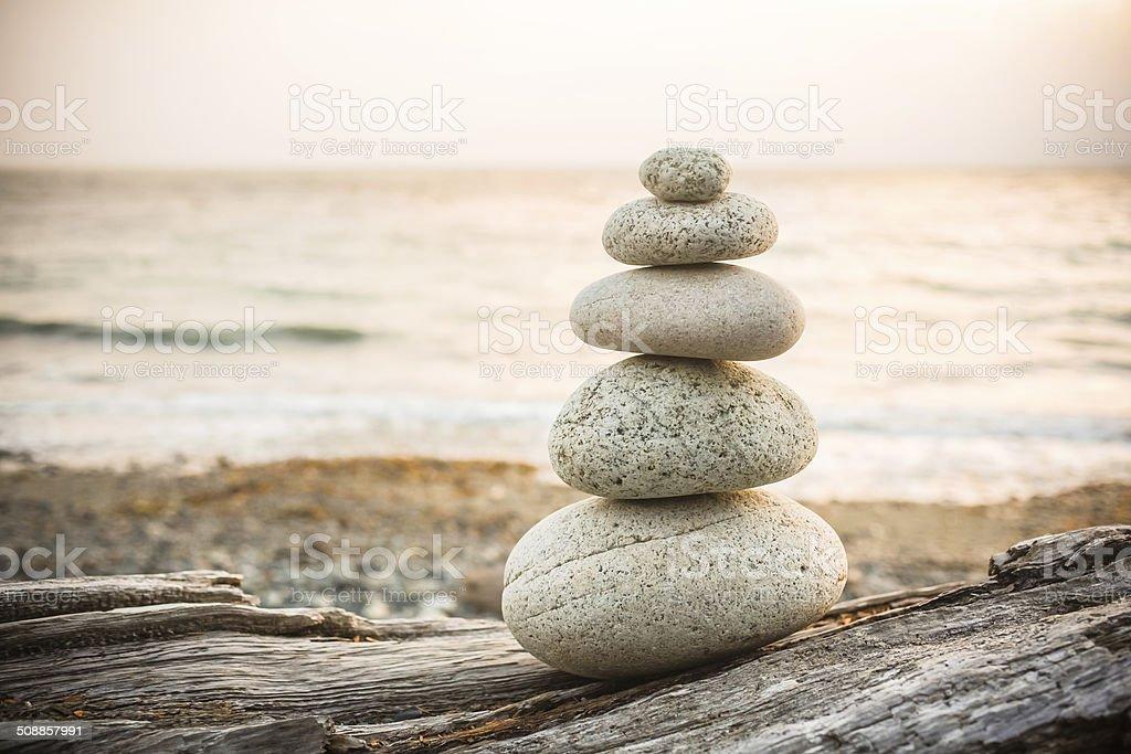 Inukshuk Cairn on driftwood on beach stock photo