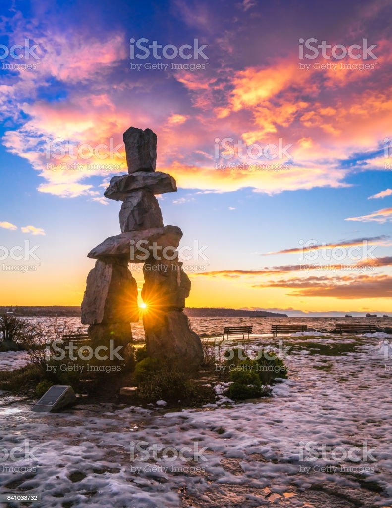 Inukshuk in the winter with sunset clouds sky backgrounds stock photo