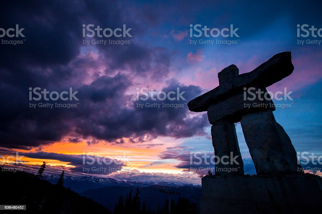 Inukshuk on top of mountain during sunset. stock photo