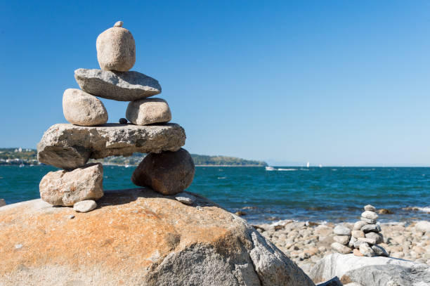 Inukshuk Rock balancing in Vancouver stone stacking garden stock photo