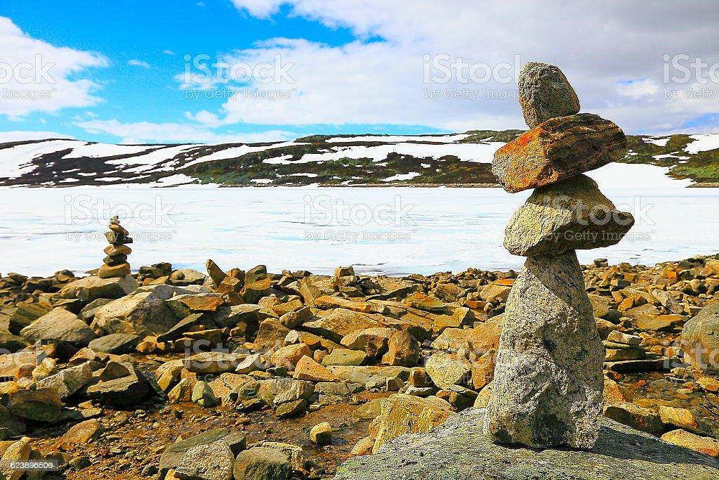 Inukshuk, Snowcapped frozen lake, mountain range - Hardanger, Norway, Scandinavia stock photo