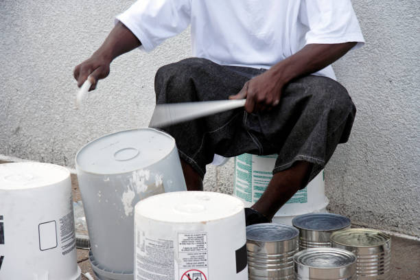 Inventive Drummer Young African American man beating out the rhythm on plastic container bucket drums. Horizontal. drummer stock pictures, royalty-free photos & images