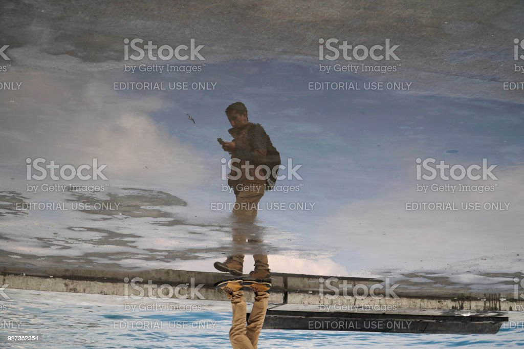 Inverse reflection of a man on water with reflection of the clouds and blue sky stock photo