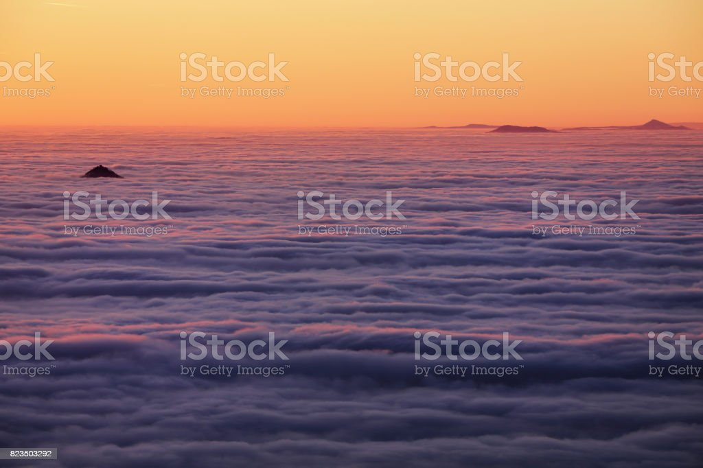 Inversion over the valley, orange-colored sky and clouds. stock photo