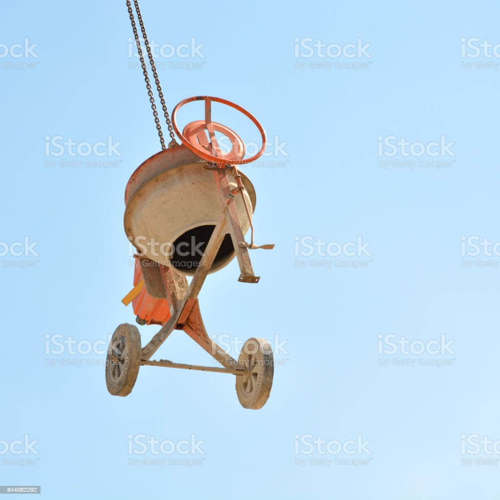 Inverted concrete mixer hanging in the air on the crane, so that it is not stolen. stock photo
