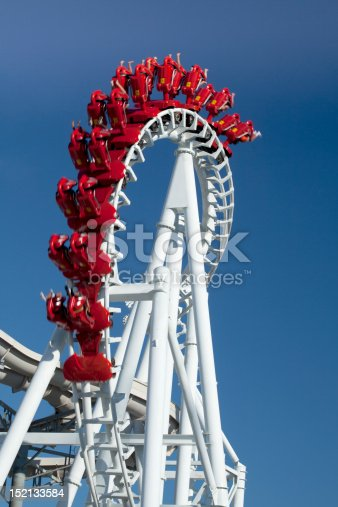 Inverted hanging rollercoaster speeding along a twisted track with clear blue sky background.