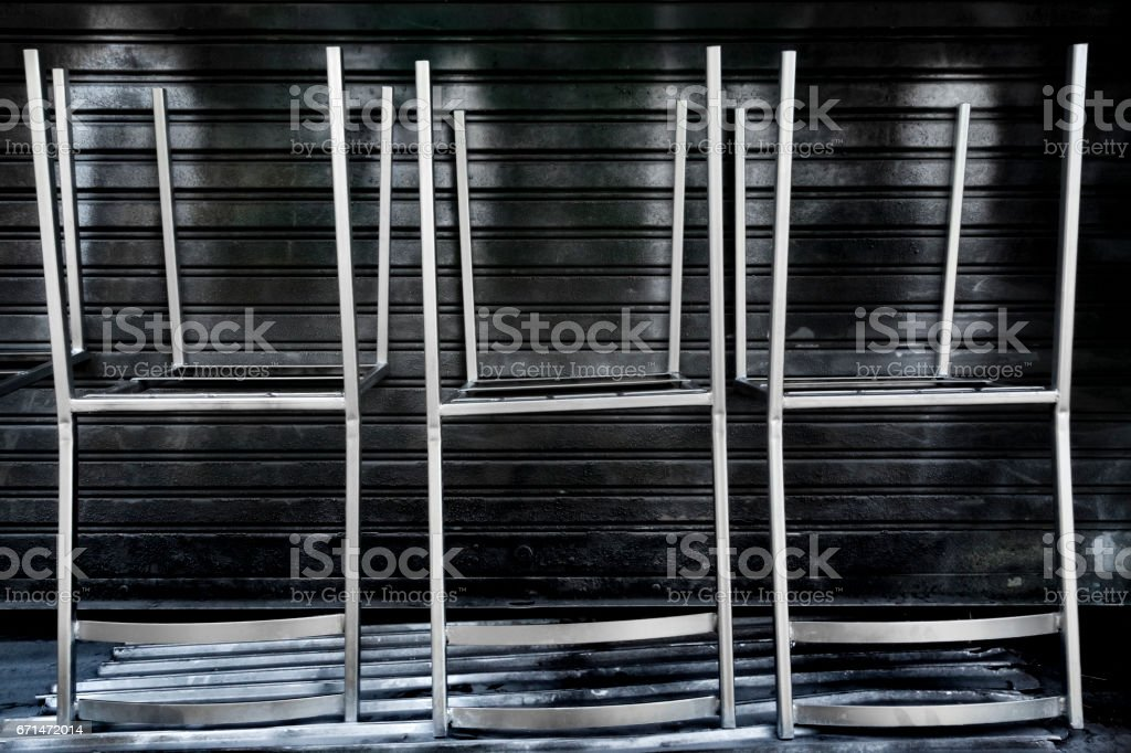 Inverted, silver spray-painted metal chairs, Chiang Mai, Thailand stock photo