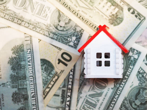 Invest in real estate, mortgage concept. White house with a red roof on the background of dollar bills Invest in real estate, mortgage concept. White house with a red roof on the background of dollar bills real estate sign stock pictures, royalty-free photos & images
