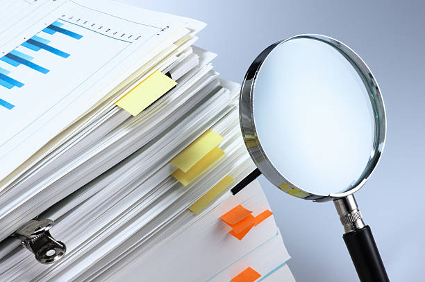 Investigate and analyze. Magnifying glass and stack of documents. scrutiny stock pictures, royalty-free photos & images