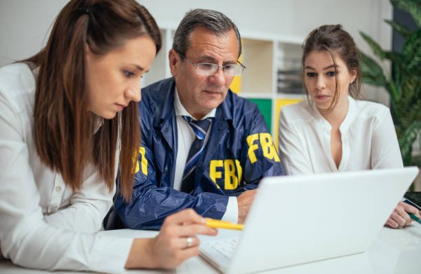 Investigating a crime A group of fbi agents, sitting in the office, investigating stuff. police meeting stock pictures, royalty-free photos & images