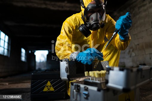 Man in protective workwear taking toxic samples at the  radioactive ruined building.
