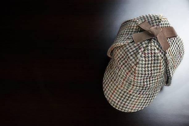 Investigation Concept With Deerstalker Hat On Black Background Sherlock Holmes Deerstalker Hat On The Black Wooden Table Background In The Back Light deerstalker hat stock pictures, royalty-free photos & images