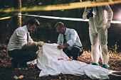 Group of people, crime scene investigation, police and forensics doing their jobs, there is a dead body in the forest.