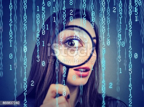 istock Investigation surveillance of cyber crime concept. Curious woman looking through a magnifying glass and computer binary code background 855837240