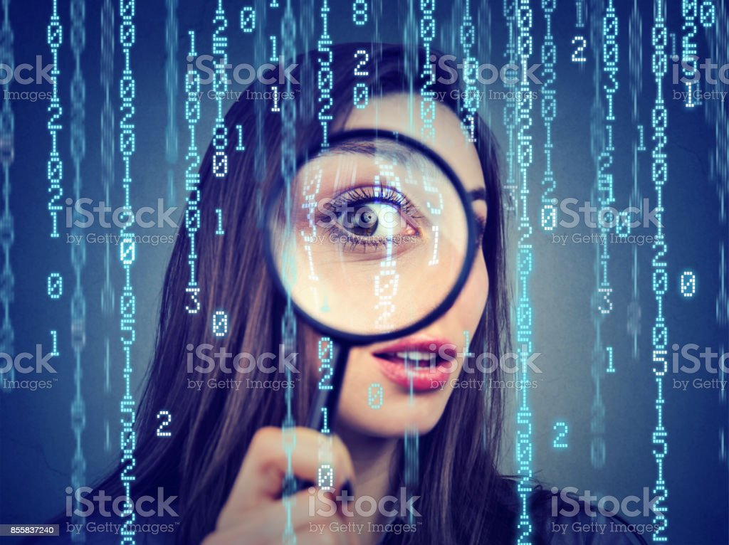 Investigation surveillance of cyber crime concept. Curious woman looking through a magnifying glass and computer binary code background stock photo
