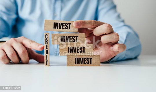 Investing and borrowing. Wooden blocks jingsaw stacked on top of each other with the inscription Invest. Business and finance concept, investing with the help of credit. The man is indebted to invest.
