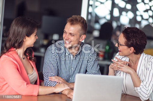 994164766 istock photo Investment adviser giving a presentation to a friendly smiling young couple seated at her desk in the office 1155525531