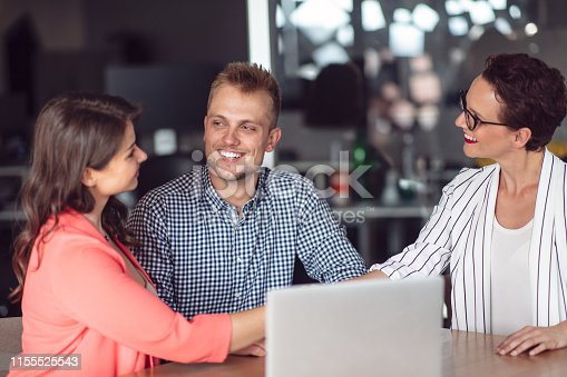 994164766 istock photo Investment adviser giving a presentation to a friendly smiling young couple seated at her desk in the office 1155525543