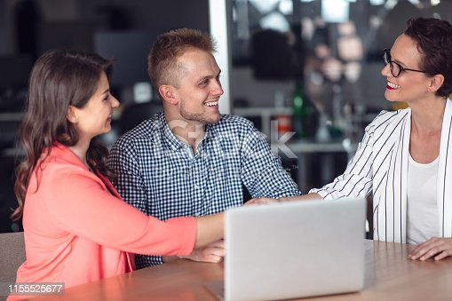 994164766 istock photo Investment adviser giving a presentation to a friendly smiling young couple seated at her desk in the office 1155525677
