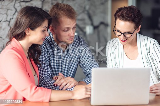 994164766 istock photo Investment adviser giving a presentation to a friendly smiling young couple seated at her desk in the office 1155525834