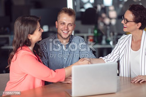 994164766 istock photo Investment adviser giving a presentation to a friendly smiling young couple seated at her desk in the office 1155527396