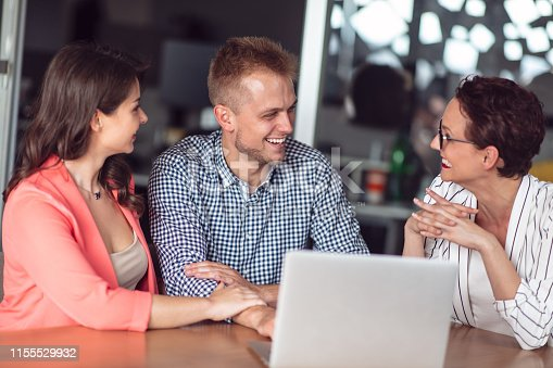 994164754istockphoto Investment adviser giving a presentation to a friendly smiling young couple seated at her desk in the office 1155529932