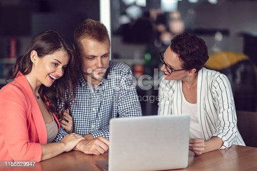 994164754istockphoto Investment adviser giving a presentation to a friendly smiling young couple seated at her desk in the office 1155529947