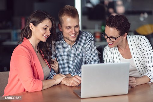 994164754istockphoto Investment adviser giving a presentation to a friendly smiling young couple seated at her desk in the office 1155532787