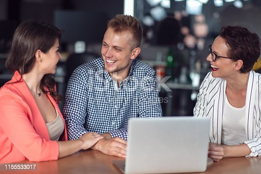 994164766 istock photo Investment adviser giving a presentation to a friendly smiling young couple seated at her desk in the office 1155533017