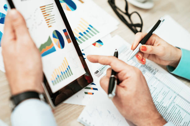 investment advisors discussing about financial markets - accountancy stock photos and pictures