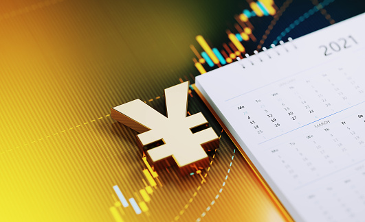 Gold colored Yen sign sitting next to the white 2021 calendar on yellow financial graph. Horizontal composition with selective focus and copy space. Investment, stock market data and financial planning concept.