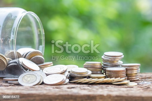 istock Investment and financial saving falling concept, Glasses and coins on table with green background 965815472