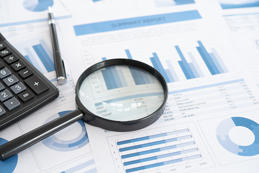 business and investment planning. Magnifying glass with business report on financial advisor desk. Concept of data analysis, accounting,audit, business research.