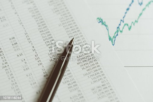 Investment, financial report statistic concept, close-up of black pen on printed stock exchange data price number or valuation table with green and blue yearly graph.
