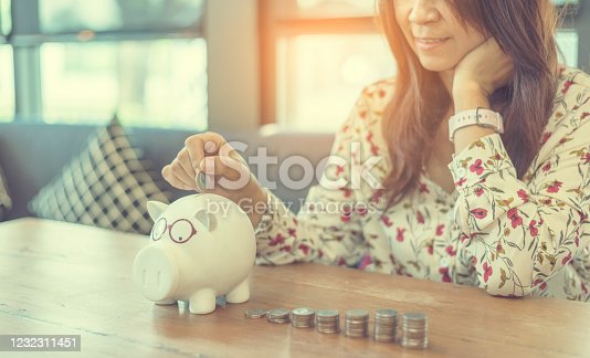 941729686 istock photo Investment Saving Money Concept. Woman hand go up on budget to buy house real estate agent. Gold coins stack symbol buy property mortgage money loan with stack of money coin 1232311451
