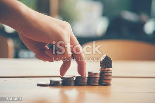 941729686 istock photo Investment Saving Money Concept. Woman hand go up on budget to buy house real estate agent. Gold coins stack symbol buy property mortgage money loan with stack of money coin 1232313521