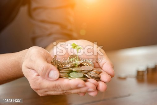 941729686 istock photo Investment Saving Money Concept. Woman hand go up on budget to buy house real estate agent. Gold coins stack symbol buy property mortgage money loan with stack of money coin 1232314031