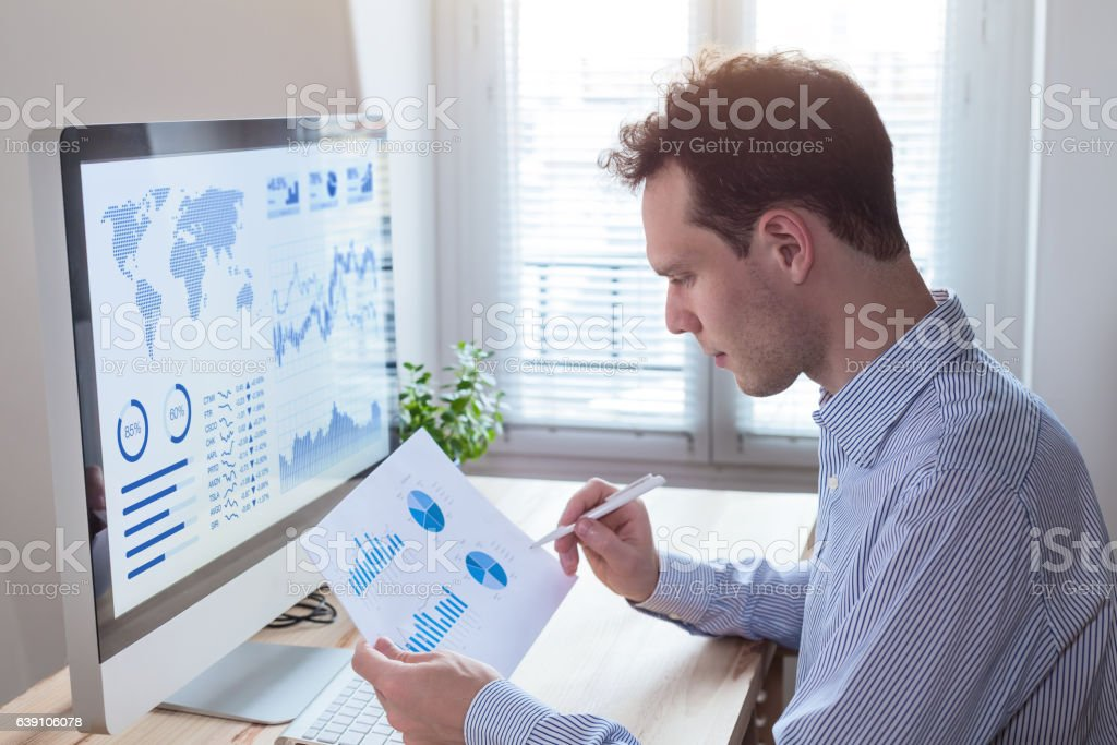 Investor analyzing financial reports and key performance indicators, computer screen stock photo