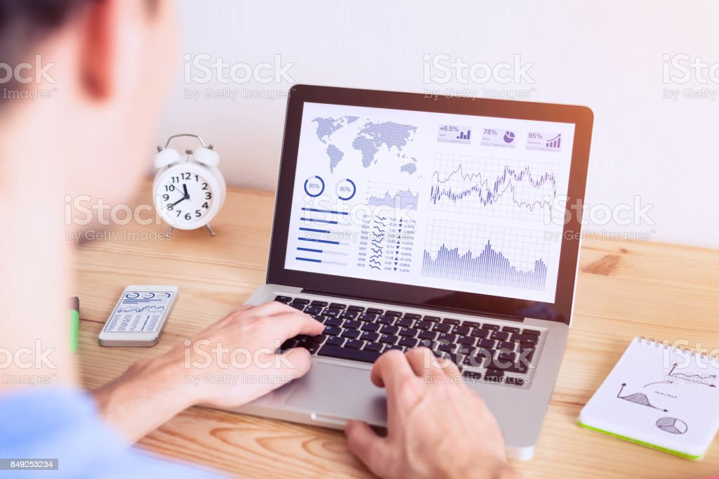 Investor analyzing online financial stock exchange graph on computer screen stock photo
