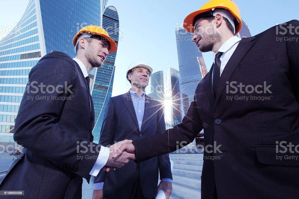 Investor and contractor shaking hands stock photo