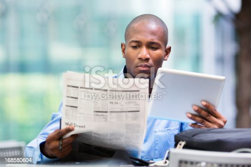 istock Investor compares quotes from newspaper and tablet 168580604