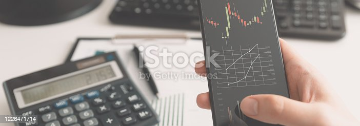 Invevstor using mobile trader app. Stock market, investment concept