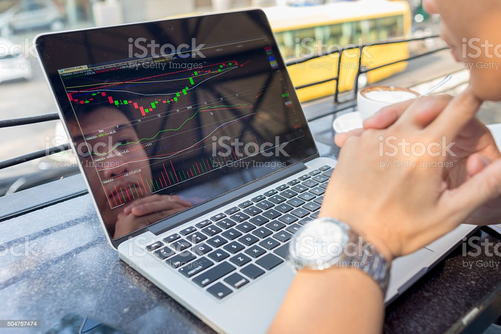 Investor watching the change of stock market on laptop stock photo