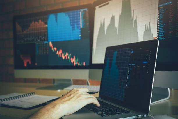 Anleger nutzen Laptops, die auf Investment-Websites auf dem Aktienmarkt einsteigen und Leistungsdaten analysieren. – Foto
