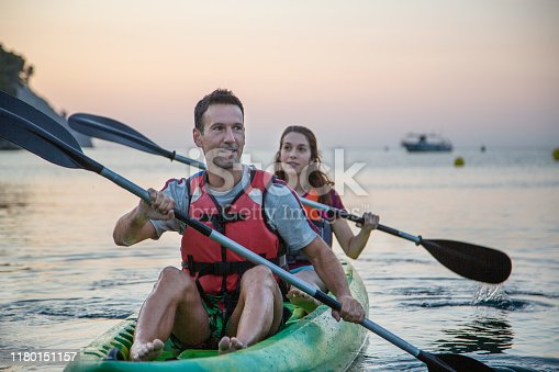Smiling Caucasian friends in 30s and 40s paddling their kayak in Mediterranean off coast of Spain at sunset.