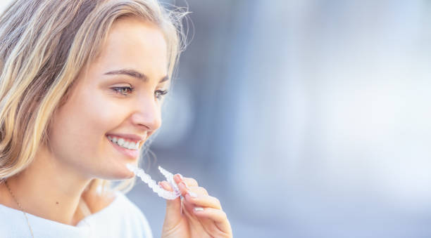 Invisalign orthodontics concept - Young attractive woman holding - using invisible braces or trainer. stock photo